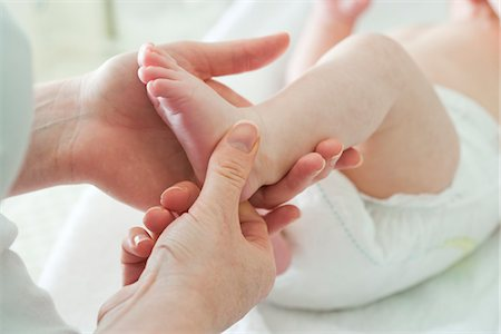 Baby's foot. Mother holding her 17 week old baby boy's foot. Stock Photo - Premium Royalty-Free, Code: 679-03681914