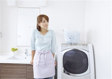 Middle-aged woman standing next to a laundry machine Stock Photo - Premium Royalty-Free, Code: 670-06024958