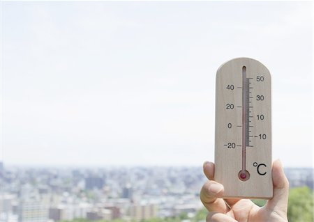 Hand holding a thermometer and a cityscape Stock Photo - Premium Royalty-Free, Code: 670-06450021