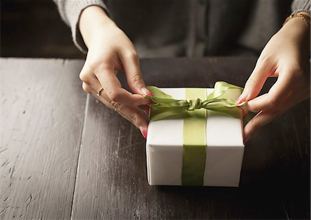 Woman tying a gift box with a ribbon Stock Photo - Premium Royalty-Free, Code: 670-06450744