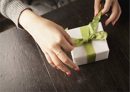 female hand - Woman tying a gift box with a ribbon Stock Photo - Premium Royalty-Free, Code: 670-06450745