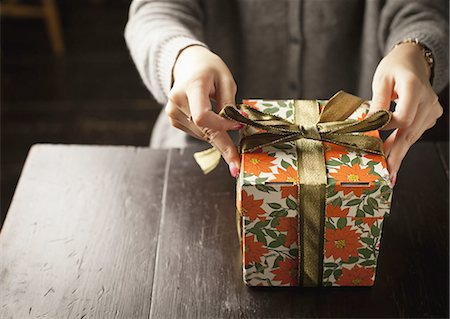 Woman tying a gift box with a ribbon Stock Photo - Premium Royalty-Free, Code: 670-06450743