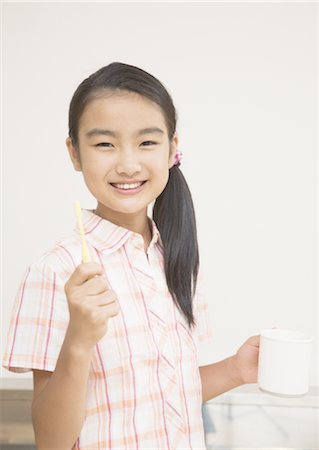 Elementary school girl holding toothbrush and cup Stock Photo - Premium Royalty-Free, Code: 670-02642629