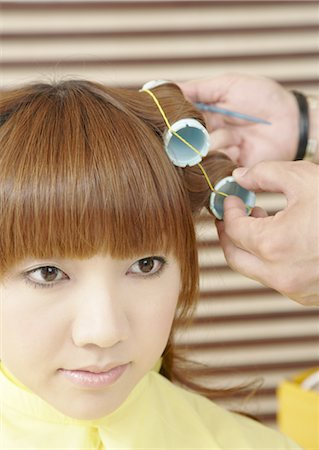 A young woman is set her hair in curlers Stock Photo - Premium Royalty-Free, Code: 670-03483837