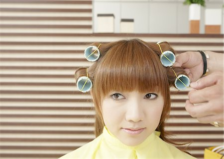 A young woman is set her hair in curlers Stock Photo - Premium Royalty-Free, Code: 670-03483838