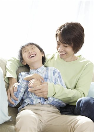 Father and son relaxing on sofa Stock Photo - Premium Royalty-Free, Code: 670-03885664