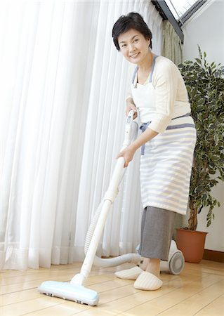 Woman vacuuming Stock Photo - Premium Royalty-Free, Code: 670-03885673