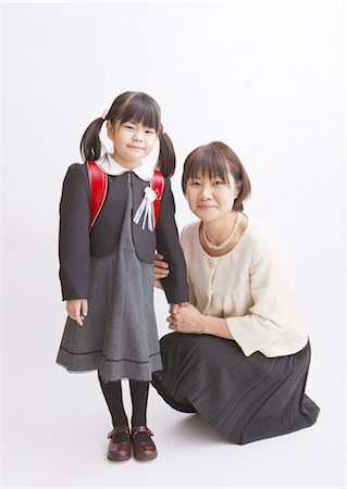 Girl carrying school bag and mother Stock Photo - Premium Royalty-Free, Code: 670-03886158