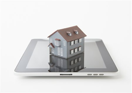 Tablet PC and miniature model house Stock Photo - Premium Royalty-Free, Code: 670-03886467