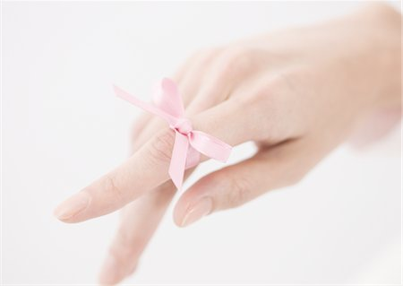 Pink ribbon tied on woman's finger Stock Photo - Premium Royalty-Free, Code: 670-03886935