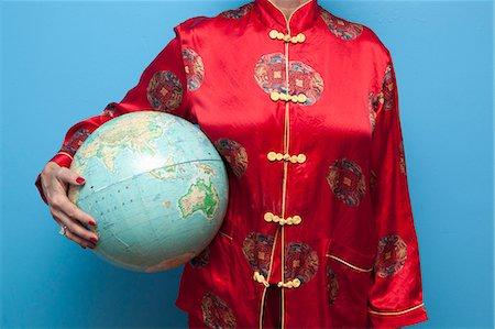 silky - Woman in Chinese pajamas holding globe Stock Photo - Premium Royalty-Free, Code: 673-06025395