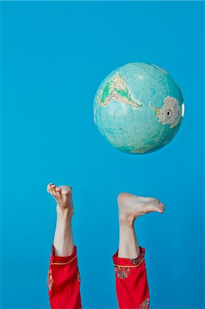 Feet kicking globe in air Stock Photo - Premium Royalty-Free, Code: 673-06025419