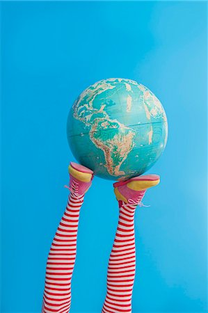 Legs in striped socks with colorful shoes holding globe Stock Photo - Premium Royalty-Free, Code: 673-06025425
