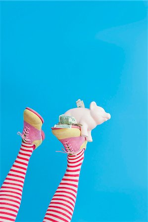Legs in striped socks with colorful shoes holding piggy bank Stock Photo - Premium Royalty-Free, Code: 673-06025427