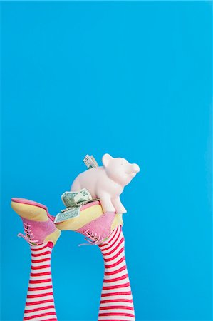 Legs in striped socks with colorful shoes holding piggy bank Stock Photo - Premium Royalty-Free, Code: 673-06025428