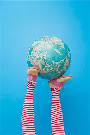 Legs in striped socks with colorful shoes holding globe Stock Photo - Premium Royalty-Free, Code: 673-06025423