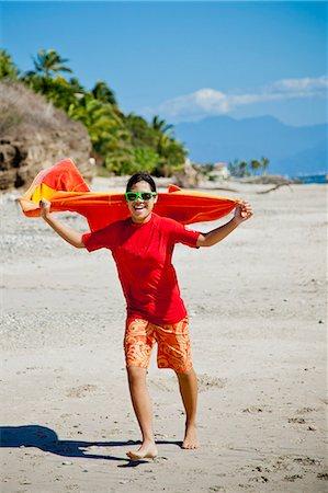 Teen girl running on beach with towel cape Stock Photo - Premium Royalty-Free, Code: 673-06025577