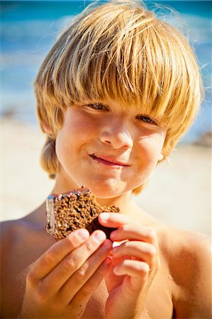 Young boy taking bite of large brownie Stock Photo - Premium Royalty-Free, Code: 673-06025579