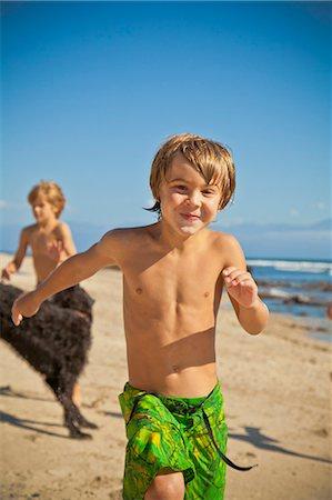 Children running on beach with dog Stock Photo - Premium Royalty-Free, Code: 673-06025581