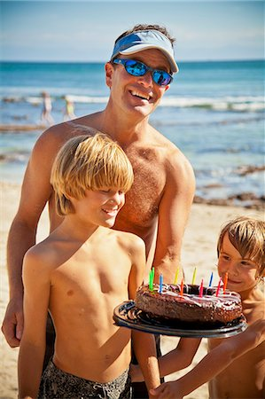 Man holding birthday cake on beach with two boys Stock Photo - Premium Royalty-Free, Code: 673-06025583