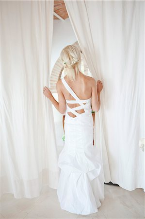 special event - Rear view of bride peeking through curtains Stock Photo - Premium Royalty-Free, Code: 673-06025625