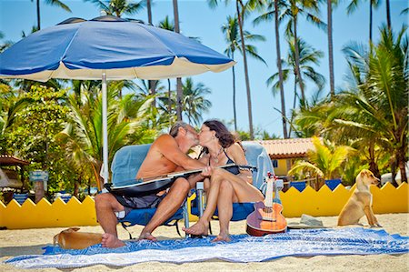 Man and woman kissing while seated in beach chairs Stock Photo - Premium Royalty-Free, Code: 673-06025654