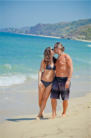 Man and woman walking on beach in swim suits Stock Photo - Premium Royalty-Free, Code: 673-06025658