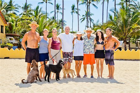 Seven adults standing on beach with dogs near palm trees Stock Photo - Premium Royalty-Free, Code: 673-06025667