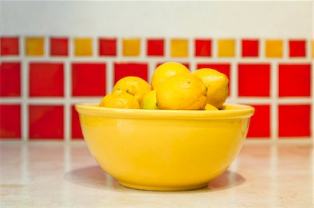 Bowl of lemons on counter with red tiles behind Stock Photo - Premium Royalty-Free, Code: 673-06025698