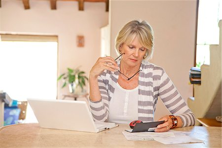 Woman working at home office with computer and bills Stock Photo - Premium Royalty-Free, Code: 673-06025726