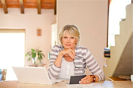 Woman working at home office with computer and bills Stock Photo - Premium Royalty-Free, Code: 673-06025728