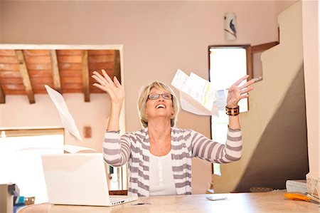 Woman at home office throwing bills in air Stock Photo - Premium Royalty-Free, Code: 673-06025746