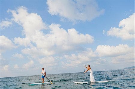 Dressed up man and woman riding paddle boards Stock Photo - Premium Royalty-Free, Code: 673-06964470