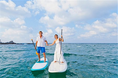 sports and sailing - Dressed up man and woman riding paddle boards Stock Photo - Premium Royalty-Free, Code: 673-06964473
