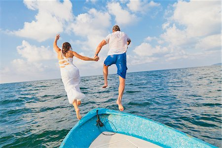 Dressed up man and woman jumping off boat Stock Photo - Premium Royalty-Free, Code: 673-06964481
