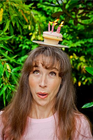 special event - Woman with birthday cupcake on head Stock Photo - Premium Royalty-Free, Code: 673-06964518