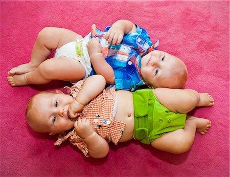 Twin babies on pink rug Stock Photo - Premium Royalty-Free, Code: 673-06964574