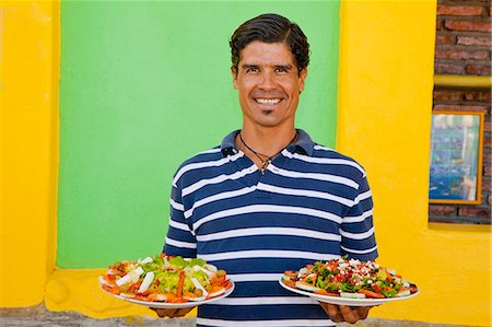 Man holding plates of mexican food Stock Photo - Premium Royalty-Free, Code: 673-06964604