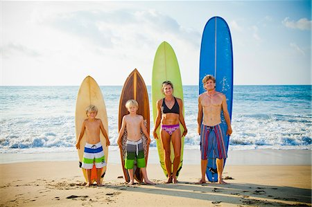 Family standing on beach with surfboards Stock Photo - Premium Royalty-Free, Code: 673-06964631