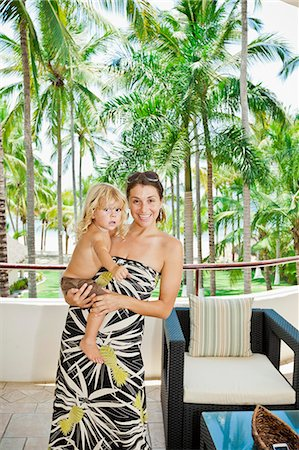 Stylish woman with baby near palm trees Stock Photo - Premium Royalty-Free, Code: 673-06964644