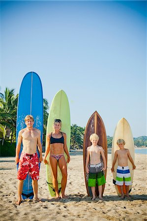 Family of four standing in front of surfboards Stock Photo - Premium Royalty-Free, Code: 673-06964641