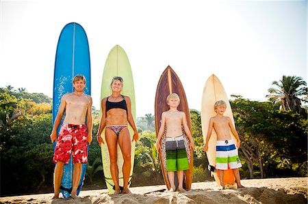 Family of four standing in front of surfboards Stock Photo - Premium Royalty-Free, Code: 673-06964642