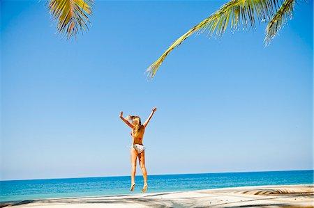 Woman in bikini jumping on beach Stock Photo - Premium Royalty-Free, Code: 673-06964733
