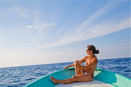 Woman sitting in bow of boat Stock Photo - Premium Royalty-Free, Code: 673-06964764