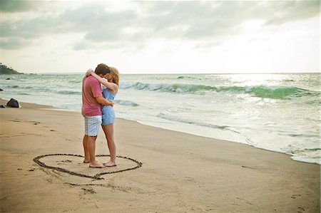 Young couple standing in heart design on beach Stock Photo - Premium Royalty-Free, Code: 673-06964772