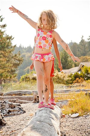 preteen bathing suit - Two children balancing on driftwood log Stock Photo - Premium Royalty-Free, Code: 673-06964808