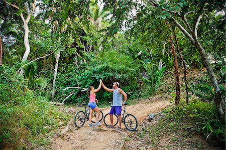 Couple riding bicycles on jungle path Stock Photo - Premium Royalty-Free, Code: 673-06964802