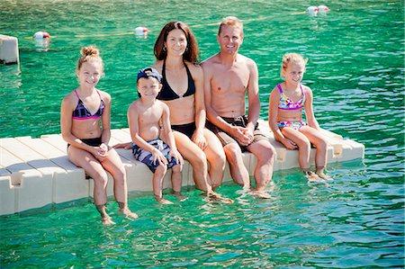 Family sitting on dock in lake Stock Photo - Premium Royalty-Free, Code: 673-06964839