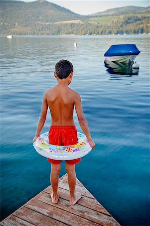 Young boy wearing float ring on dock Stock Photo - Premium Royalty-Free, Code: 673-06964844