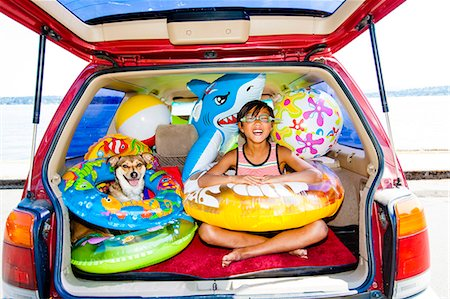 preteen swim - Child poses with his dog in the open trunk of a car full of beach toys and floaties Stock Photo - Premium Royalty-Free, Code: 673-08139159
